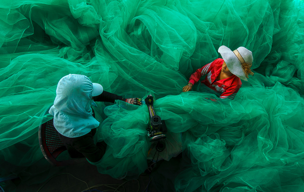 22. woman sewing the fishing net