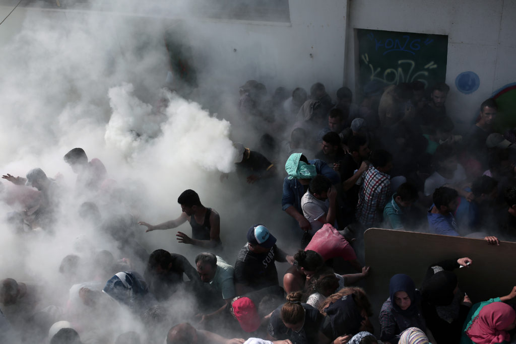 Policemen try to disperse hundreds of migrants and refugees by spraying them with fire extinguishers during a gathering for a registration procedure at the stadium on the Greek island of Kos, on August 11, 2015. Police on the Greek island on Kos hit migrants and refugees with truncheons to prevent a stampede, a day after an officer was caught on camera slapping a migrant.